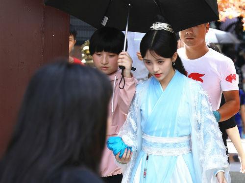 鞠婧祎蓝色古装长裙显清丽 获助理撑伞气派十足