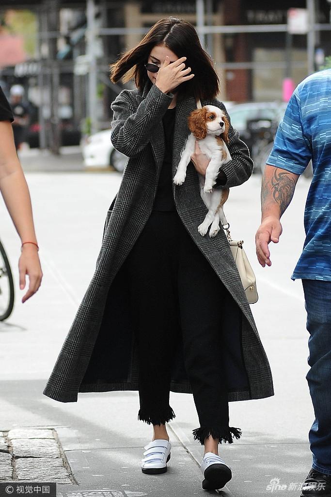 赛琳娜穿格子风衣气场强 与宠物狗上演亲亲抱抱
