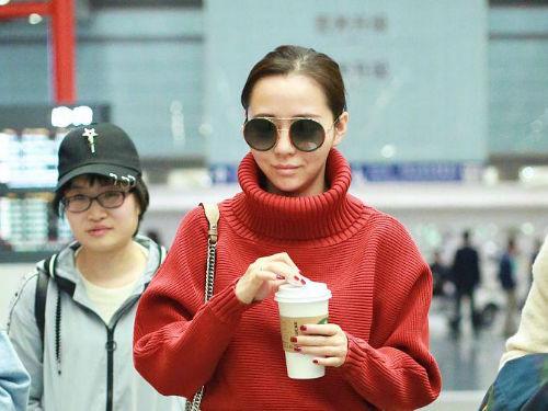 张靓颖扎马尾似邻家姐姐 穿大红高领毛衣喝咖啡取暖