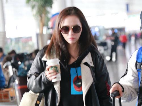 张靓颖披头散发现身机场忙着喝饮料 见镜头露齿一笑暖心可人