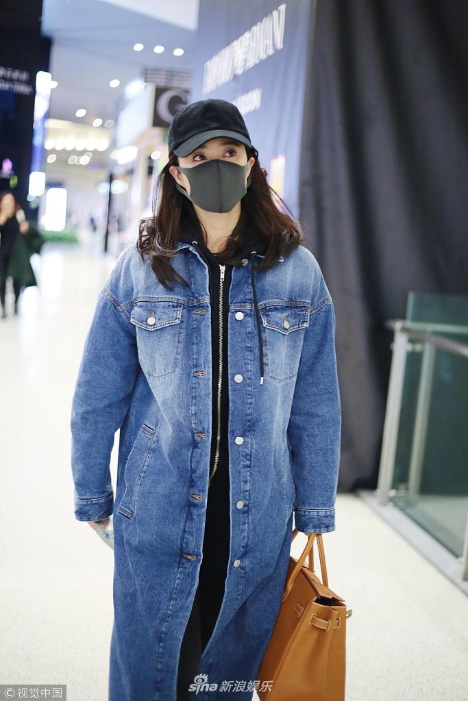 蒋欣现身机场穿牛仔长褂显肥圆 全副武装低调赶路