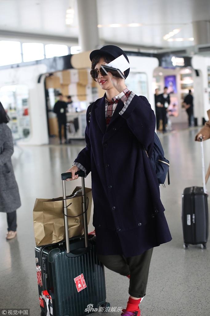 张歆艺现身机场齐刘海配大檐帽红袜子 挥手挡脸拒绝拍照