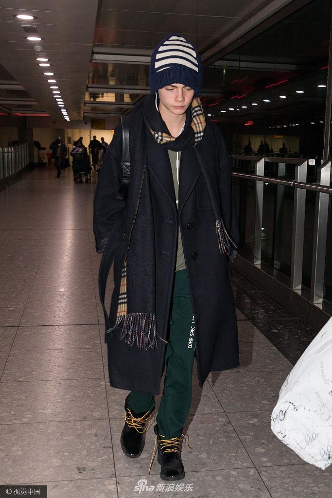 卡拉・迪瓦伊现身机场戴帽子裹围巾 鞋带松开未察觉