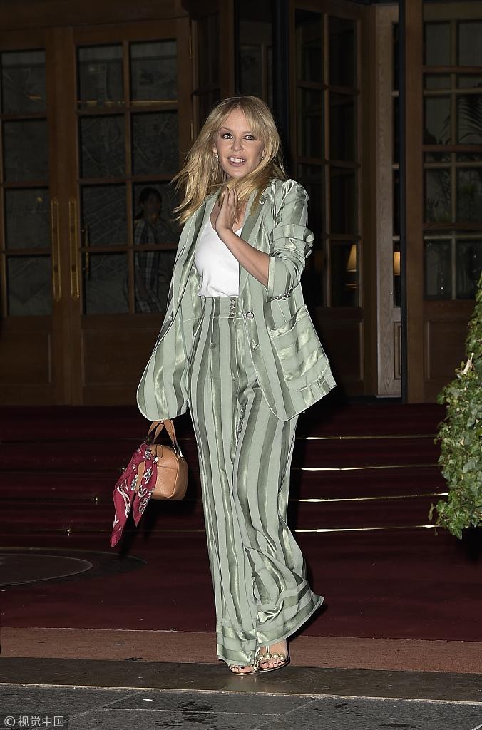 凯莉・米诺一头金色长发飞扬 绿丝绸西装摇曳生姿露迷人笑容