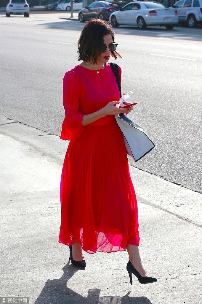 珍娜・迪万身着红色翩跹长裙火辣性感 低头玩手机懒理镜头