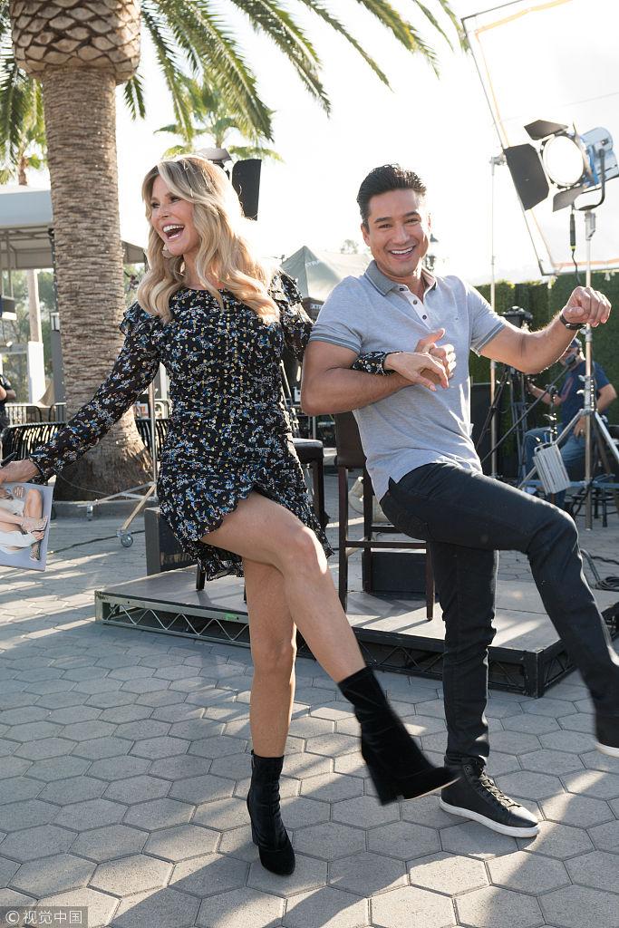 克里斯蒂现身《Extra》花裙秀美腿 与马里奥洛佩兹相挎踢腿