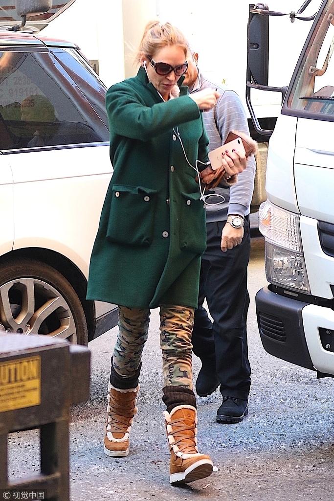 乌玛・瑟曼马尾辫减龄边走边听歌 绿大衣搭迷彩裤造型清新