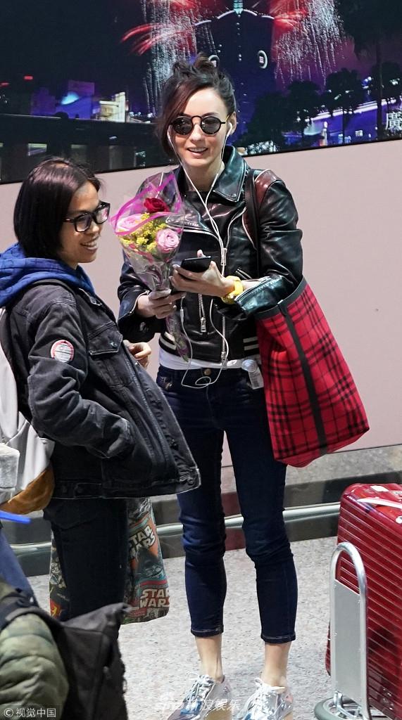 张柏芝梳高马尾现身机场 获粉丝接机送花心情大好仰天大笑
