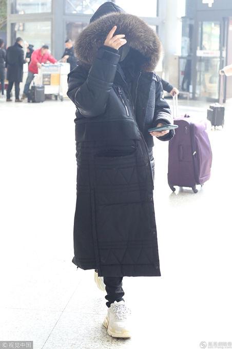 宁静现身机场把自己裹成粽子 脱帽安检露凌乱短发和辣眼妆容