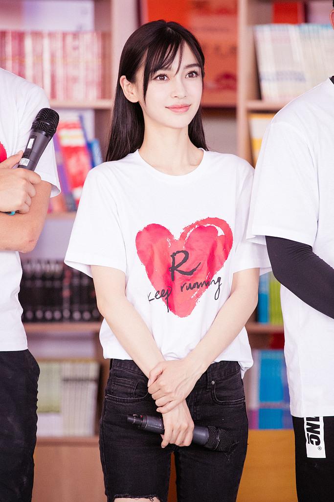 Baby穿红心T恤清纯可人 做公益与学生踢球