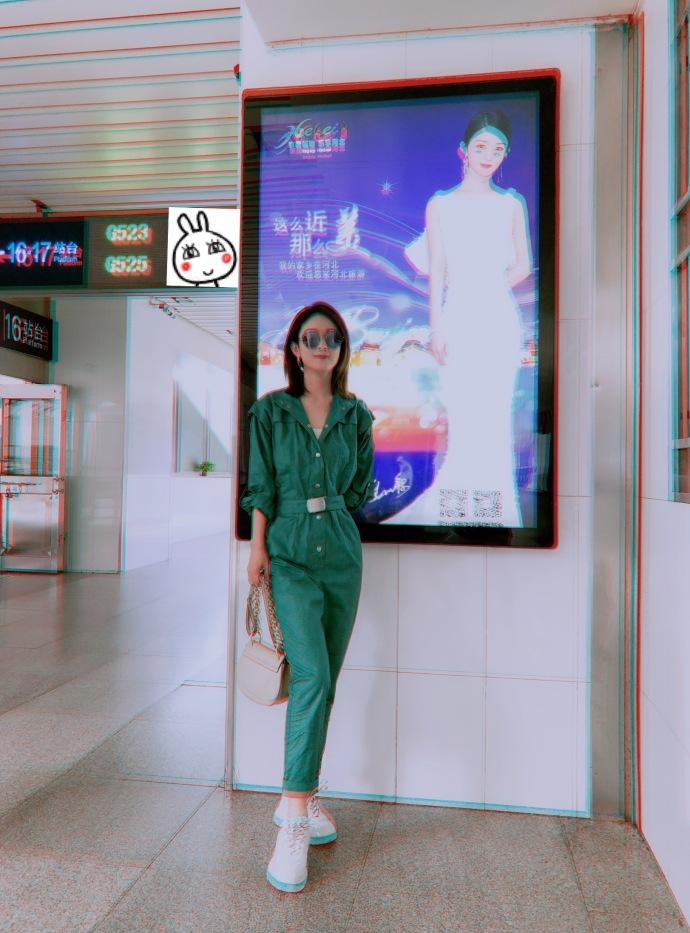 赵丽颖与自己的广告合影 身着绿色连体衣